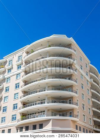 A modern stucco condo building with Large Curved Balconies poster