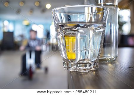 Glass With Clear Water Stands On The Edge Of A Wooden Table, Carelessly Left With The Possibility Of