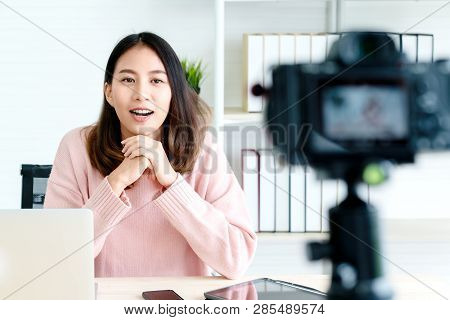Young Attractive Asian Woman Blogger Or Vlogger Looking At Camera And Talking On Video Shooting With