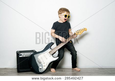 Childrens Hobbies: A Little Boy In Black Glasses Plays The Electric Guitar, Imitates A Rock Star.