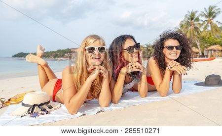 Three Young Beautiful Girlfriends In Bikini Relaxing On A Tropical Beach, Travel And Vacation Concep