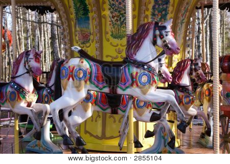 Colorful ponies on a decorated in old-style merry-go-round poster