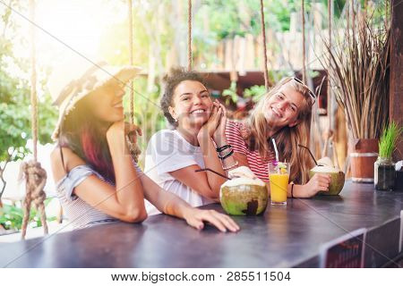Three Young Beautiful Slender Girlfriends Drink Necks And Coconuts In A Stylish Beach Bar At Counter