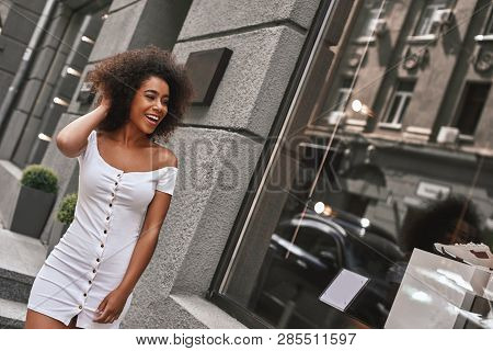 City Girl With A Great Style. Beautiful Afro American Woman In Hite Dress Playing With Her Hair Whil