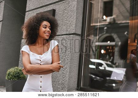 Young And Full Of Energy. Portrait Of Gorgeous Afro American Woman Standing Outdoors With Crossed Ar