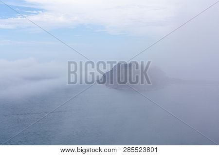 Small Island With Light House Hidden Under Low Mist And Clouds Over Ocean