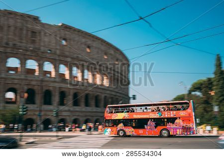 Rome, Italy - October 21, 2018: Colosseum. Red Hop On Hop Off Touristic Bus For Sightseeing In Stree