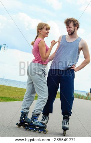 Active Holidays, Exercises, Relationship Concept. Woman And Man Wearing Rollerskates Standing And Lo