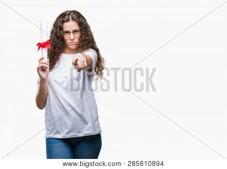 Young brunette girl holding degree and wearing glasses over isolated background pointing with finger to the camera and to you, hand sign, positive and confident gesture from the front