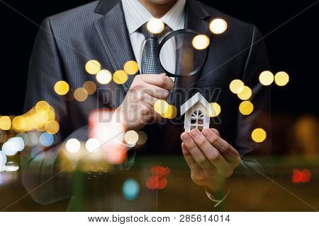 A Closeup Of A Businessman Looking At The House Model Through The Magnifier At The Blurred Backgroun
