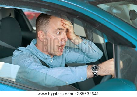 Side Window View Of Inexperienced Anxious Motorist. Young Man Driving A Car Shocked About To Have Tr