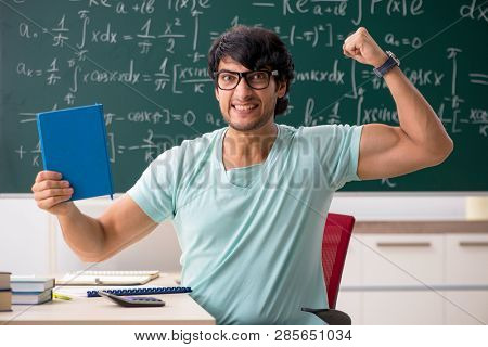 Young male student mathematician in front of chalkboard