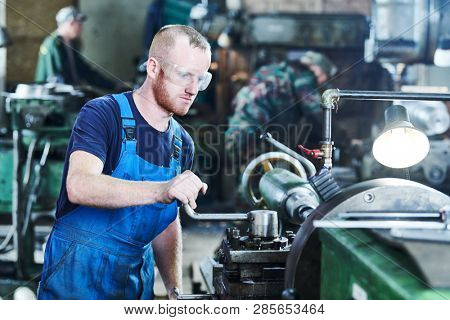 worker turner operating lathe machine at industrial manufacturing factory