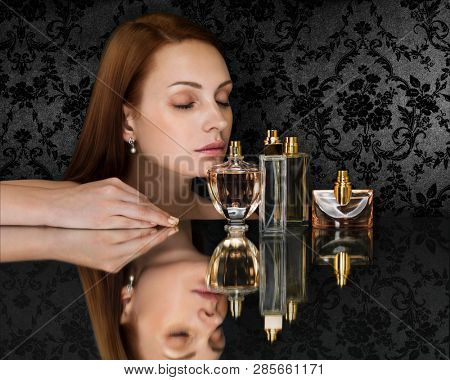 Beautiful woman and collection of perfumes bottles on dark background. Space for text.