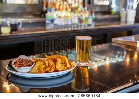 Mexican nacho chips and salsa dip dish on a bar background