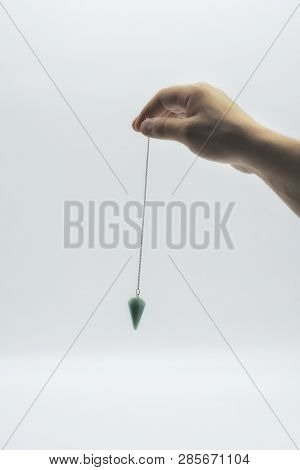 Pendulum Dowsing On An Isolated White Background With A Turquoise Crystal.
