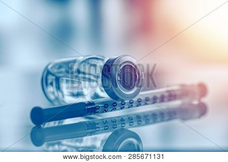 Closeup Of Medicine Vial Or Flu, Measles Vaccine Bottle With Syringe And Needle For Immunization On