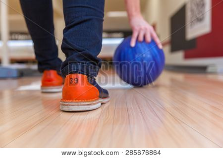 Man With A Bowling Ball Playing Bowling At A Bowling Alley In The Sports Center