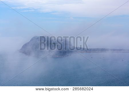 Low Clouds Above The Ocean Hiding Moored Sailboats And Barrenjoey Lighthouse In Sydney, Australia