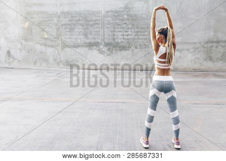 Fitness woman in sportswear doing stretching exercise on the city street over gray concrete background. Outdoor sports clothing and shoes, urban style.