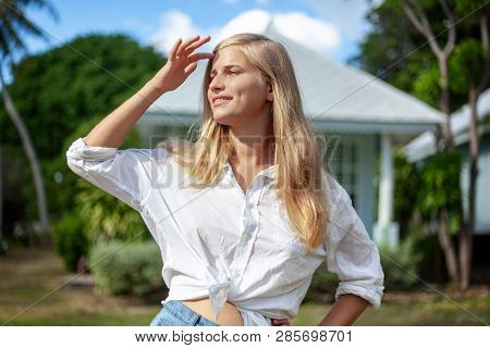 Beautiful Young Blonde Woman At Summer Green Lawn, Enjoys The Sun Spring And Summer. Beautiful Woman