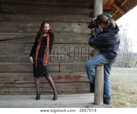 Man Takes A Photograph Of Teenage Girl Against Timber Wall