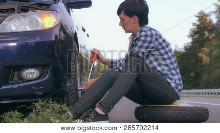 Young Woman Stuck On The Side Of The Road With A Flat Tire. Caucasian Brunette Driver Change A Tire
