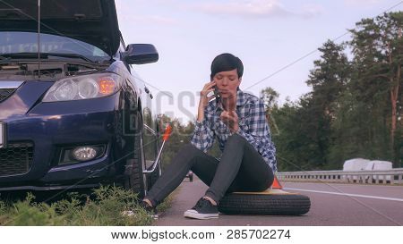 Young woman stuck on the side of the road with a flat tire. Girl sitting on the spare tire at the roadside calling for help or has phone conversation with friend. poster