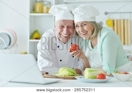 Portrait Of Senior Couple At Kitchen Cooking With Laptop