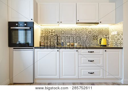 Beautiful home kitchen with white cabinets and backlight poster