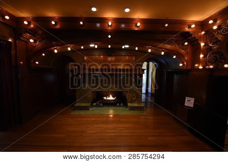 Dimly Lit Fire Place In A Room With Dark Hard Woods And Vintage Light Bulbs At Pleasant Home, Oak Pa