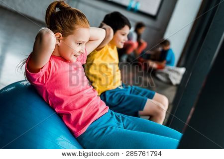 Cheerful Kids Doing Abs Exercise With Fitness Balls