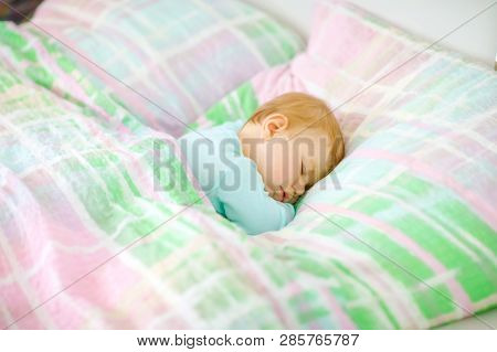 Adorable Little Baby Girl Sleeping In Bed. Calm Peaceful Child Dreaming During Day Sleep. Beautiful