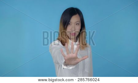 Young Asian Woman Posing Showing Hand Gesture Stopping On Blue Background In Studio. Attractive Mill