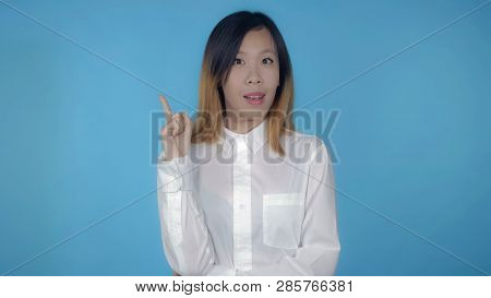 Young Asian Woman Posing Showing Hand Gesture Find Decision On Blue Background In Studio. Attractive