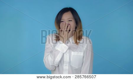 Young Asian Woman Tired And Overworked On Blue Background In Studio. Attractive Millennial Girl Wear