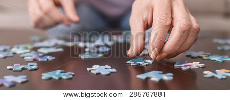 Alzheimers Disease, Dementia, Memory Loss And Mental Health Concept. Hands Of Old Woman With Jigsaw