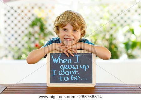 Happy Little Kid Boy With Chalk Desk In Hands. Healthy Adorable Child Outdoors On Desk When I Grow U