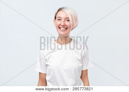 Woman With Short Dyed Hair Being Very Glad Smiling With Broad Smile Showing Her Perfect Teeth