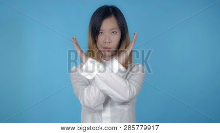 Young Asian Woman Posing Showing Hand Gesture Stopping Refuse On Blue Background In Studio. Attracti