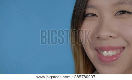 Close Up Portrait Part Face Young Asian Woman On Blue Background In Studio. Attractive Millennial Gi