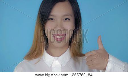 Close Up Portrait Young Asian Woman Laughing Shows Sign Like On Blue Background In Studio. Attractiv