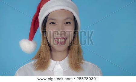 Close Up Portrait Young Asian Woman Posing Wearing Santa Claus Hat On Blue Background In Studio. Att