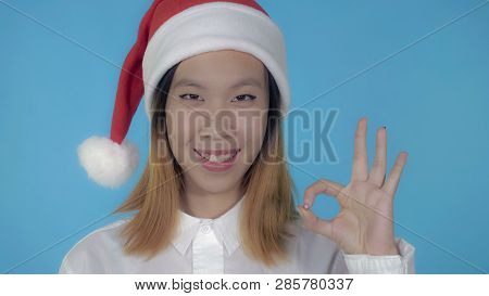 Close Up Portrait Young Asian Woman Shows Symbol Okey Wearing Santa Claus Hat On Blue Background In