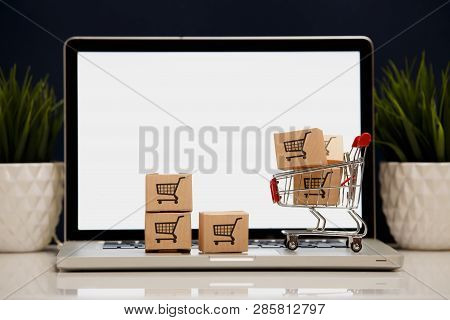 Many Paper Boxes In A Small Shopping Cart On A Laptop Keyboard. Concepts About Online Shopping That