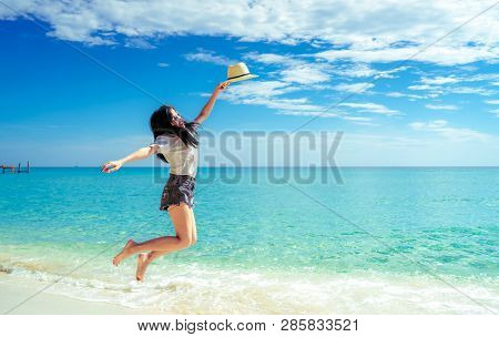 Happy Young Woman In Casual Style Fashion And Straw Hat Jumping At Sand Beach. Relaxing And Enjoy Ho