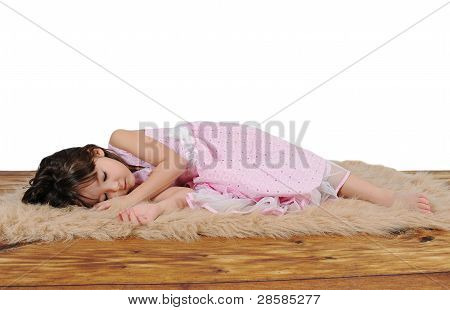 Adorable Little Girl In Dress Asleep On Furry Brown Rug. Isolated
