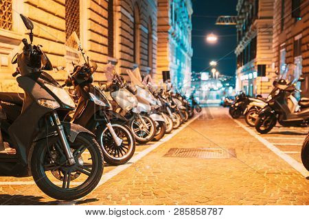 Many Motorbikes, Motorcycles Parked In European City. Scooters Parked On Night Street In European Ci