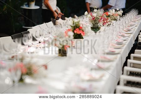 Bouquets Of Flowers And Crystal Dishes Decorated On A White Table.