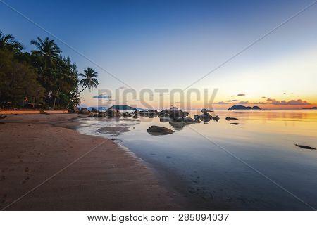 Sea Sunset Rocks Beach On Blue Sky Background. Beauty Evening Sunrise. Blue Background. Sandy Beach